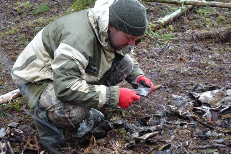 Специалист ЦСИ Сергей Катков рассматривает найденную деталь самолета