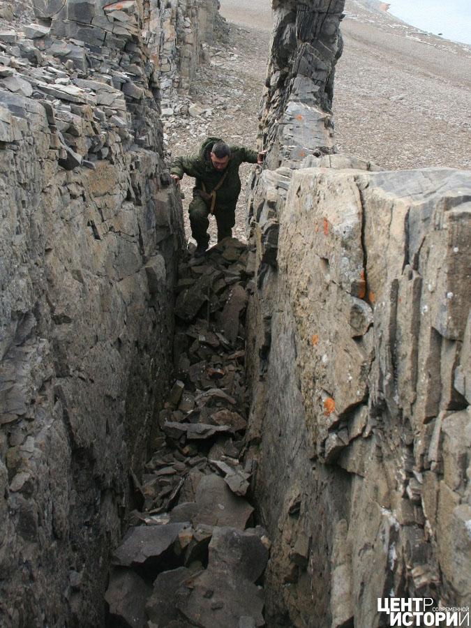 В узкой расщелине, среди глыб и щебня, виден выступающий кусочек доски. Фото: Сергей Катков